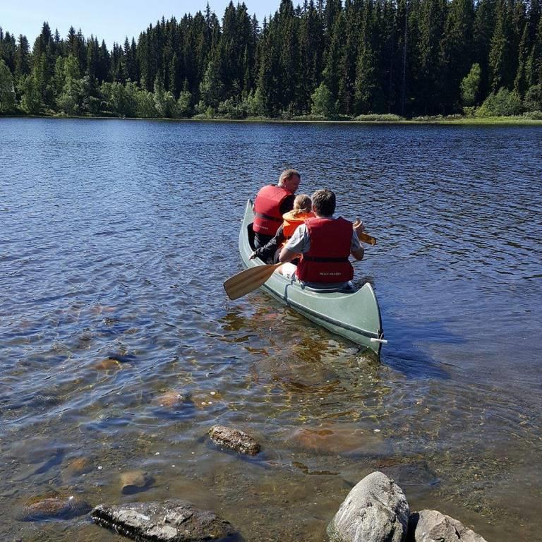 tre som padler i en kano på et vann