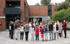 Barn og voksne som synger broderringen mens de står i ring og holder hverandre i hendene