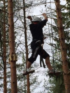 gutt som klatrer i taubane mellom trær