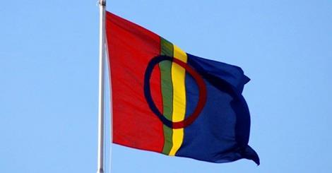 Bildet viser det samiske flagget som vaier i vinden mot blå himmel