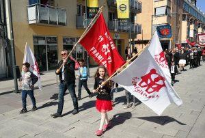 glade barn og voksne som marsjerer i 1.maitog