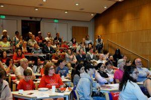 Viser mange møtedeltagere som sitter i et auditorium