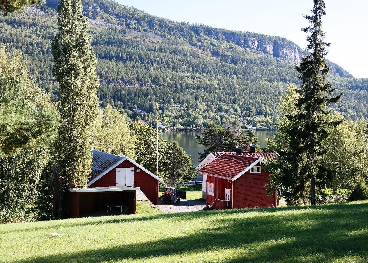 bildet viser et lite gårdstun på Utøya, bildet er tatt i solskinn