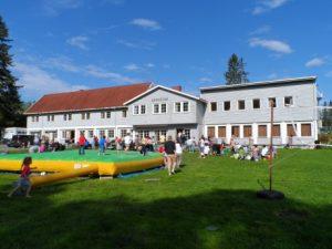 viser Skogstad Leirsted på Eina, ser skolebygget og uteplassen med mange barn og unge ute og leker