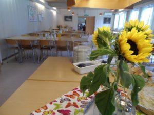 fra en spisesal, lyse farger og en bukett solsikker på bordet