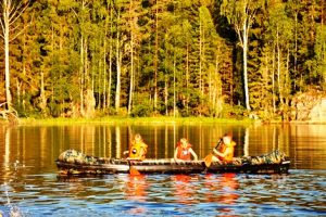 tre barn padler kano, alle har på seg redningsvest