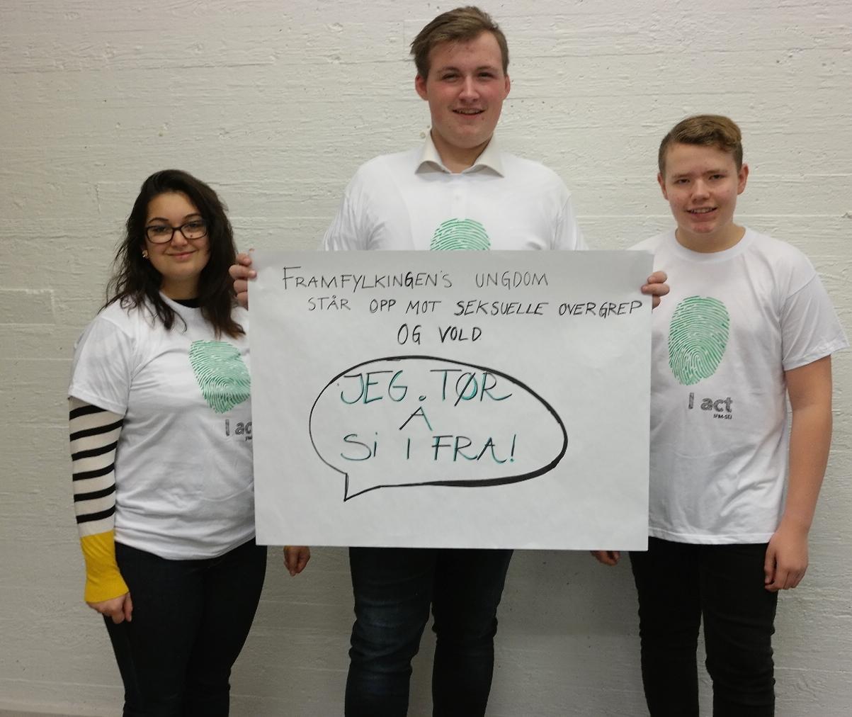 Viser tre ungdommer med en kampanjeplakat