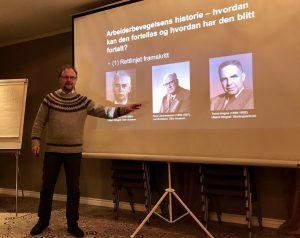 bilde av en mann som holder foredrag og peker på bilder på et lerret