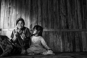 bildet viser ung jente som ser på at en eldre dame syr, hun lærer å sy