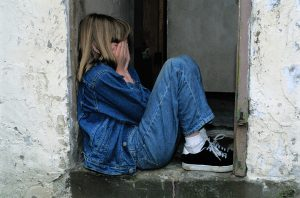 et barn som sitter og gjemmer hodet i hendene