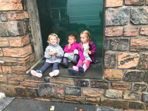 tre jenter som sitter i en vinduskarm og spiser is