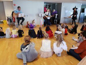 viser to som sitter foran en gruppe utkledde barn og spiller gitar og synger