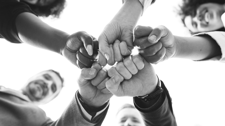 bildet viser fem knyttede never som møter hverandre i en sirkel, skal symbolisere samhold og styreke